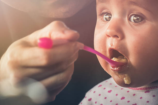 Feeding a five month old baby with a spoon stock photo