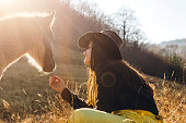 Young woman sitting on meadow and feeding foal.