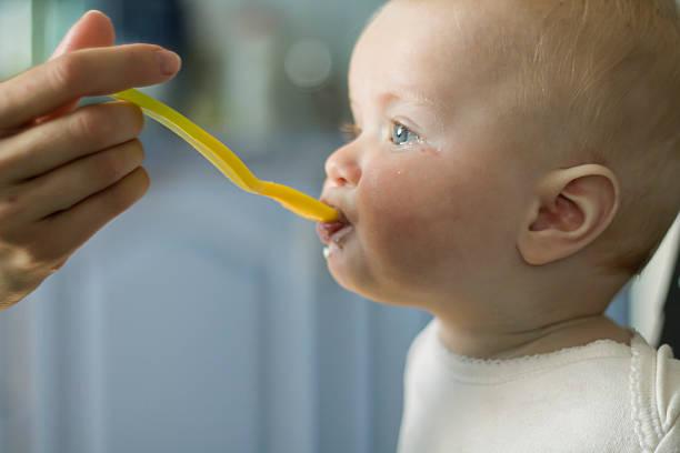 Feeding Baby Girl from Yellow Spoon stock photo