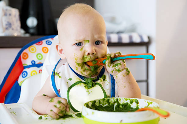 feeding. baby's first solid food - nutrire foto e immagini stock