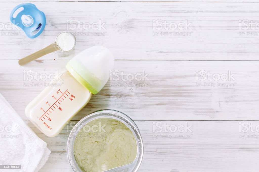 Feeding bottles and baby milk on wooden table stock photo