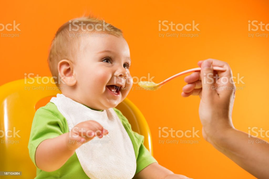 Feeding cheerful baby on orange background stock photo
