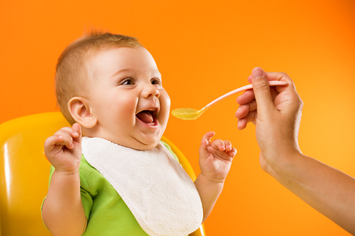 Mother's hand feeding an excited funny baby with bib in front of a vivid orange background.