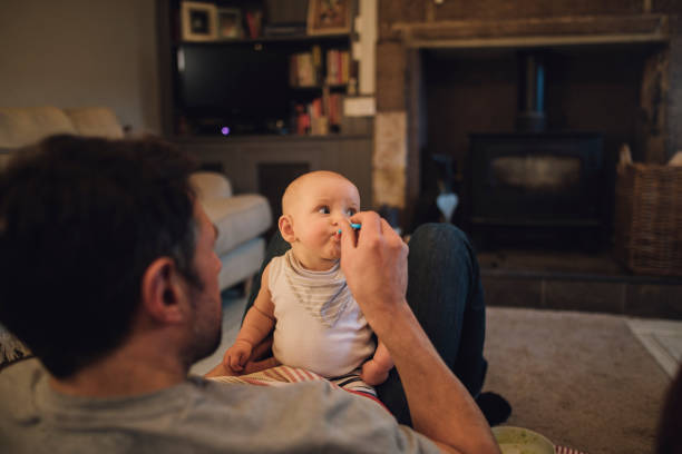 alimentación en la sala de estar - padre que se queda en casa fotografías e imágenes de stock