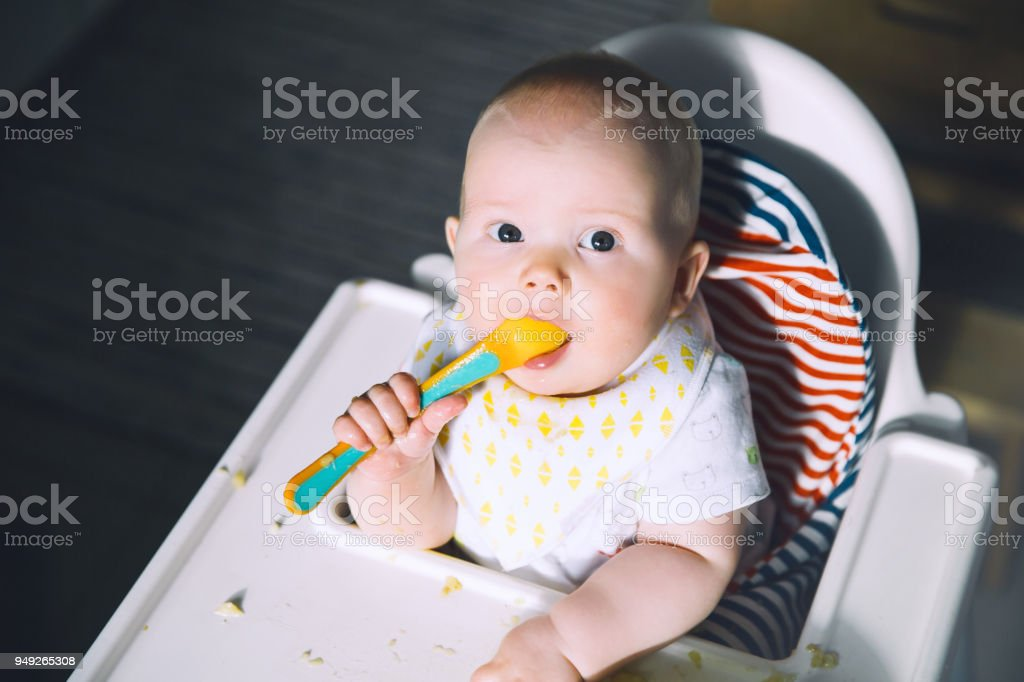 Feeding Messy Smiling Baby Eating With A Spoon In High Chair Babys