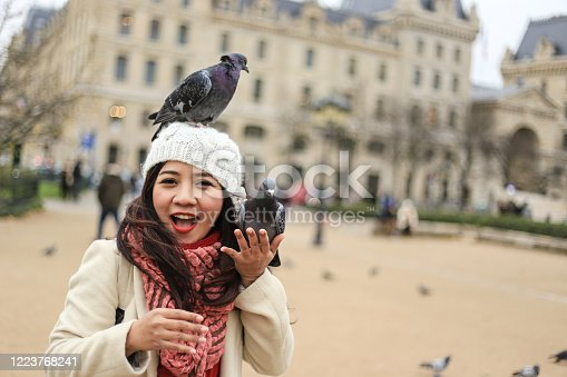 istock Feeding Pigeons at Notre Dame Cathedral Paris France 1223768241