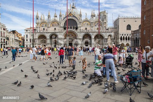 Young women feeding pigeons on St. Mark's square, Venice, Italy.