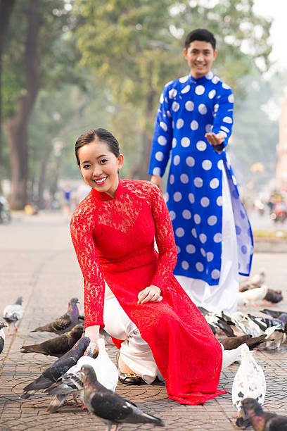 feeding pigeons - ao dai stock photos and pictures