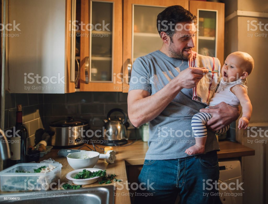 Feeding The Baby Father is standing in the kitchen of his home with his baby in his arms. He is feeding him with a spoon and spinach and vegetables can be seen on the worktop with a blender. 30-39 Years Stock Photo