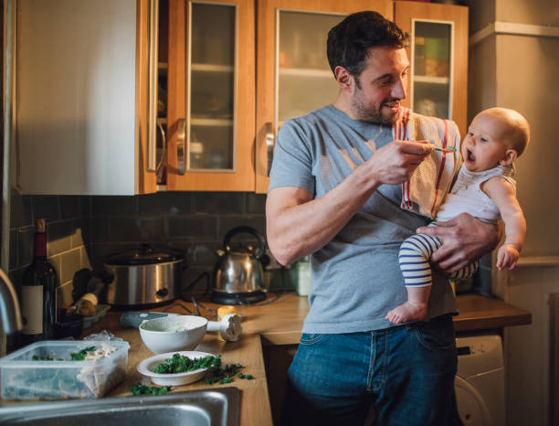 Feeding The Baby Father is standing in the kitchen of his home with his baby in his arms. He is feeding him with a spoon and spinach and vegetables can be seen on the worktop with a blender. stay at home father stock pictures, royalty-free photos & images
