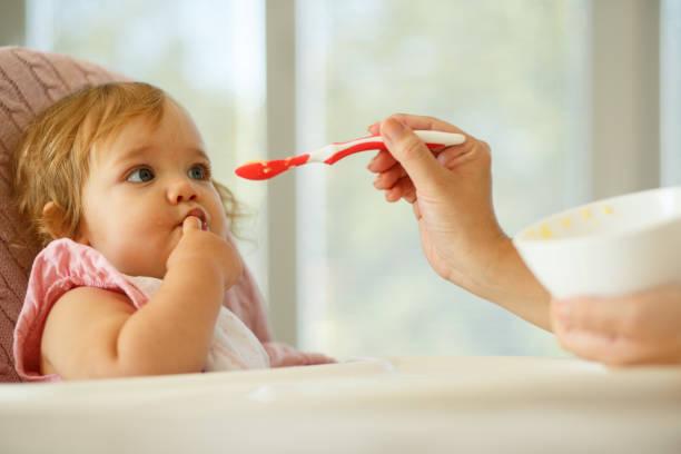 das baby füttern - kinderstuhl und tisch stock-fotos und bilder
