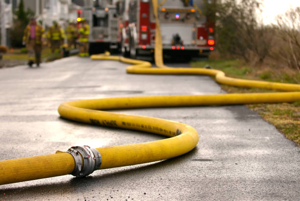 Feeding the Engine Long fire hose snakes it way from the hydrant to the pumper/engine truck in the distance coupling device stock pictures, royalty-free photos & images
