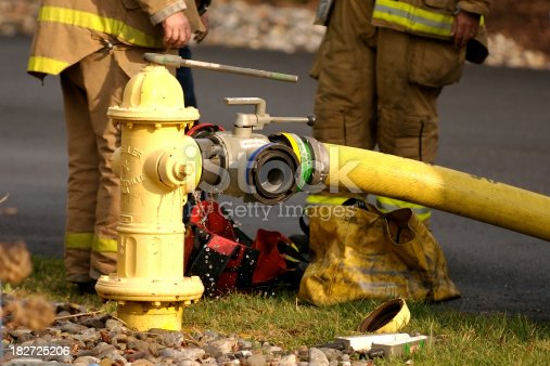 Fire fighters adjust the water pressure on a yellow fire hydrant