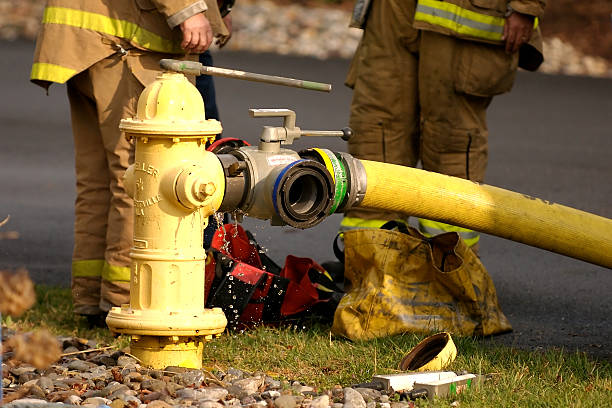 Feeding the hose Fire fighters adjust the water pressure on a yellow fire hydrant fire hydrant stock pictures, royalty-free photos & images