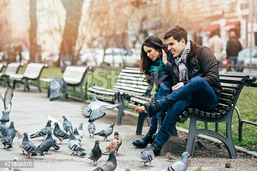 A  happy couple sitting on a bench and feeding the pigeons.