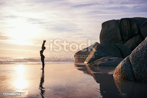 Full length shot of an attractive young woman stretching and practicing yoga on the beach at sunset