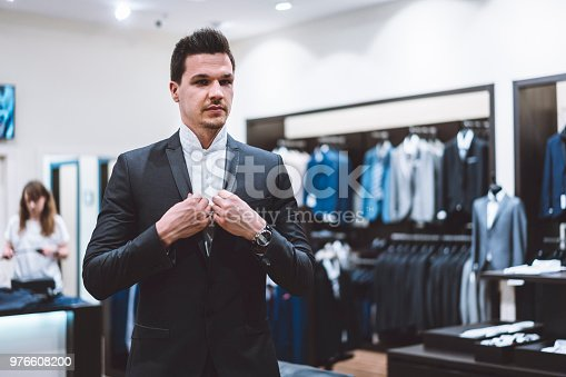 Handsome young businessman in a retail store trying on a business suit for his new job. He's tried on many different suits but he likes the classic black one the most.