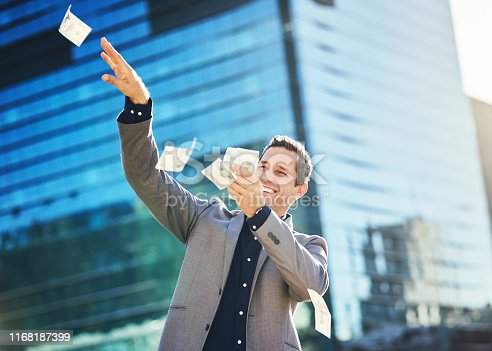 Shot of a cheerful young businessman throwing money in the air in the city