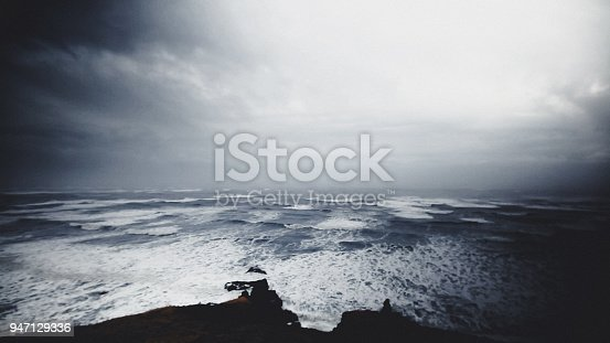 High ground view of majestic endless waves hitting the shore. Clouds are dark gray, showing that there is storm coming. Waves are starting to be big, and they are constantly hitting the rock on the shore.