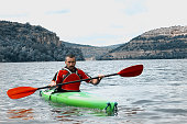 Close up of a mature man kayaking in a mountain lake. Beauty in nature, and the feeling of the endless waterfront.
