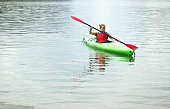 Close up of an active woman kayaking in a mountain lake. Beauty in nature, and the feeling of the endless waterfront.