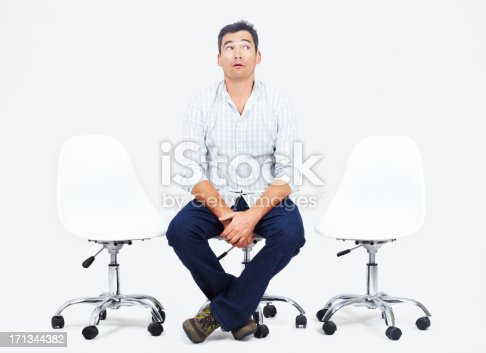 Confused adult male sitting on a white office chair glancing upwards