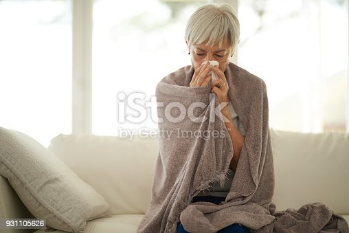 Shot of a senior woman blowing her nose with a tissue at home