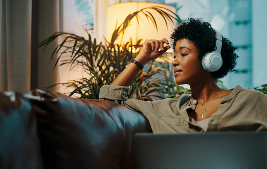 Shot of a young woman wearing headphones while sitting at home with her laptop