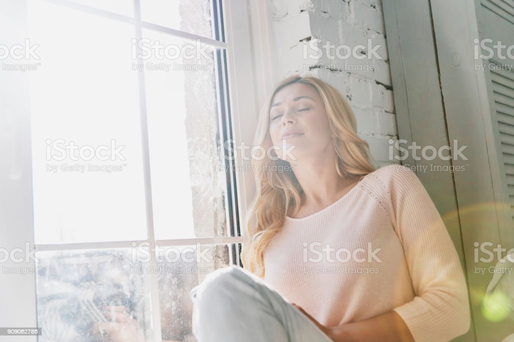 Feeling calm and happy. Attractive young woman keeping eyes closed and smiling while sitting on the window sill at home Adult Stock Photo