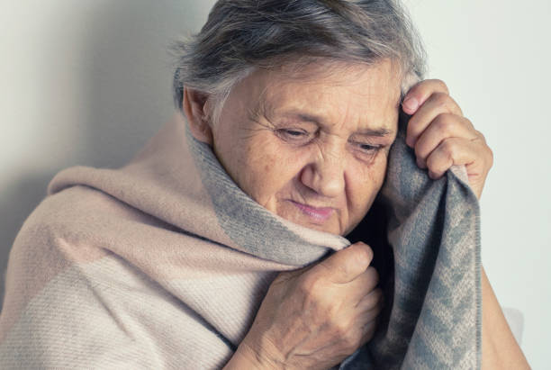 Feeling cold. Portrait of a cheerless aged woman while feeling cold. Older  woman is having flu and sneezing from sickness seasonal virus problem. Fever and cold in senior people with influenza illness stock photo