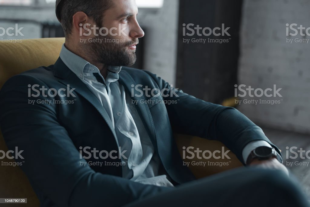 Feeling comfortable in his style Feeling comfortable in his style. Top view of handsome young man in full suit looking away while sitting on the sofa Adult Stock Photo