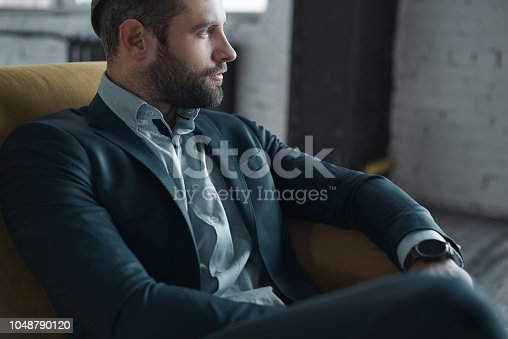 Feeling comfortable in his style. Top view of handsome young man in full suit looking away while sitting on the sofa