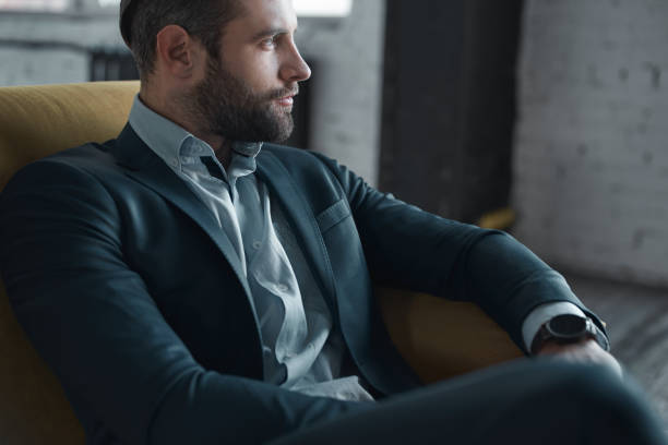 Feeling comfortable in his style Feeling comfortable in his style. Top view of handsome young man in full suit looking away while sitting on the sofa grace stock pictures, royalty-free photos & images