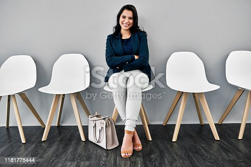 Studio shot of a young businesswoman waiting in line against a grey background