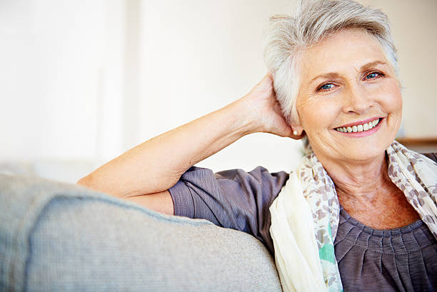 Feeling content with her life Smiling senior woman relaxing at home 65 69 years stock pictures, royalty-free photos & images