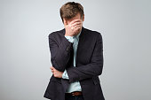 istock Feeling depressed concept. Exhausted young man in suit covering face with hand 1039710166