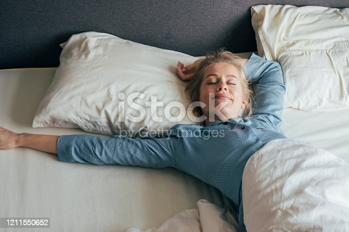 Smiling young woman stretching her arms in bed on a sunny morning.