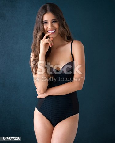 Studio portrait of an attractive young woman posing in lingerie against a dark background
