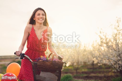 Beautiful, young woman riding a bicycle with basket of lilac and balloons, through the orchard full of trees in bloom.