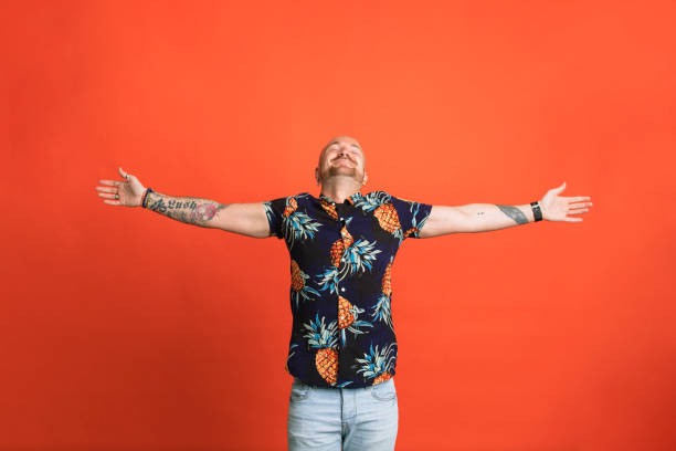 Feeling Free Portrait of a man with his head tipped back and arms outstretched standing in front of an orange studio background. arms outstretched stock pictures, royalty-free photos & images