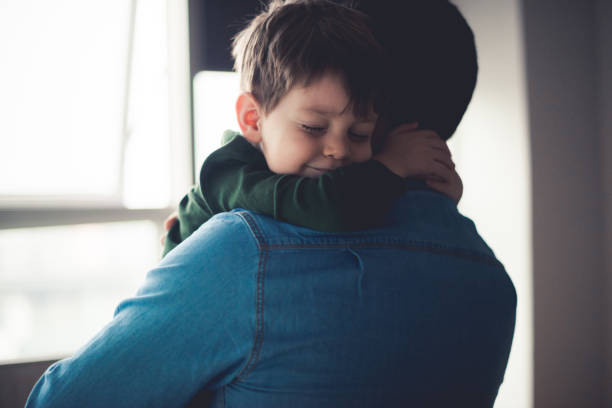 Feeling happy in dad's arms Dad and cute little son sharing an emotional hug. father stock pictures, royalty-free photos & images