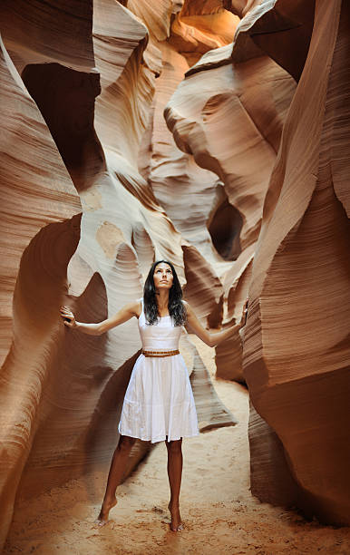 Feeling Nature (XXXL) Beautiful model standing in a hidden slot canyon looking up in the sky. Selective focus on her expression. Nikon D3X + Tripod. Ambient Light. sun shining through dresses stock pictures, royalty-free photos & images