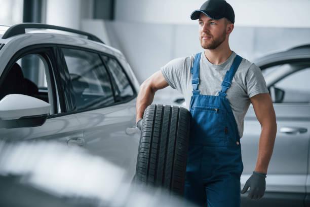 Fühlen Sie sich schön. Mechaniker hält einen Reifen in der Werkstatt. Austausch von Winter- und Sommerreifen – Foto