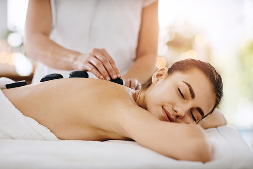 Shot of a young woman getting hot stone therapy at a spa