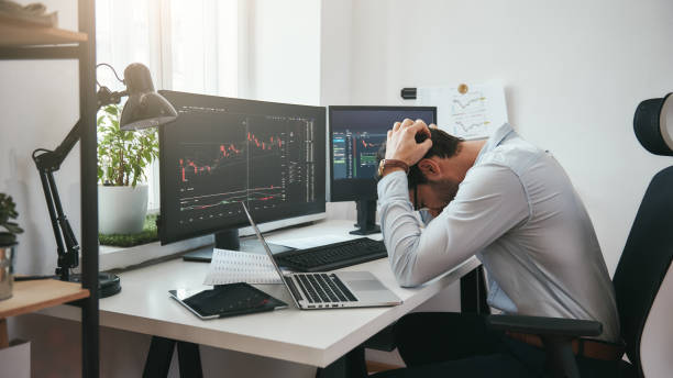 feeling sad. depressed young businessman or trader in formalwear keeping head in hands while working in the office. computer screens with trading charts and financial data. - tenersi la testa tra le mani foto e immagini stock