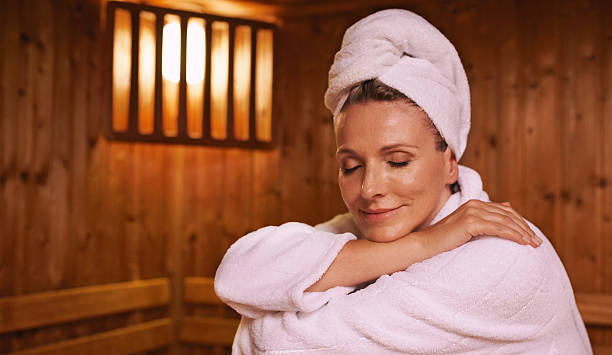 Feeling serene in the sauna Shot of a mature woman in a sauna sauna stock pictures, royalty-free photos & images