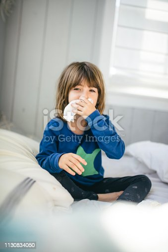 Cute little girl, age 5, holds a tissue and sits in bed looking like she's feeling very sick, a bad cold or flu perhaps. She wears pajamas and it is daytime. She is at home in bed and it is clear she is feeling very unwell