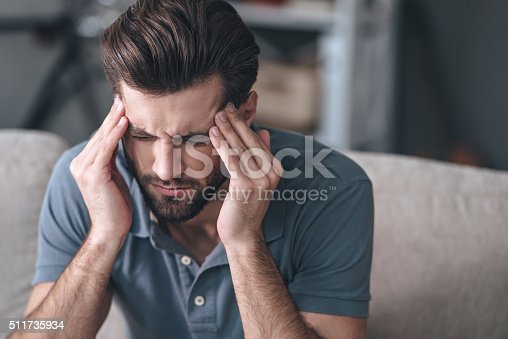Frustrated handsome young man touching his head and keeping eyes closed while sitting on the couch at home