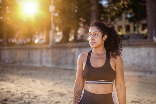 Portrait of a beautiful black female wearing exercise clothes. Standing at the beach and looking ahead at the water. Sunset shot.