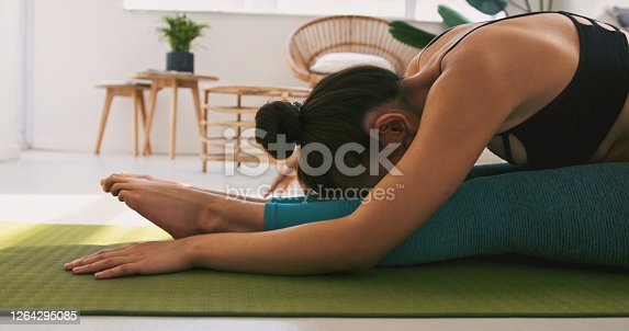 Shot of a young woman practicing yoga at home